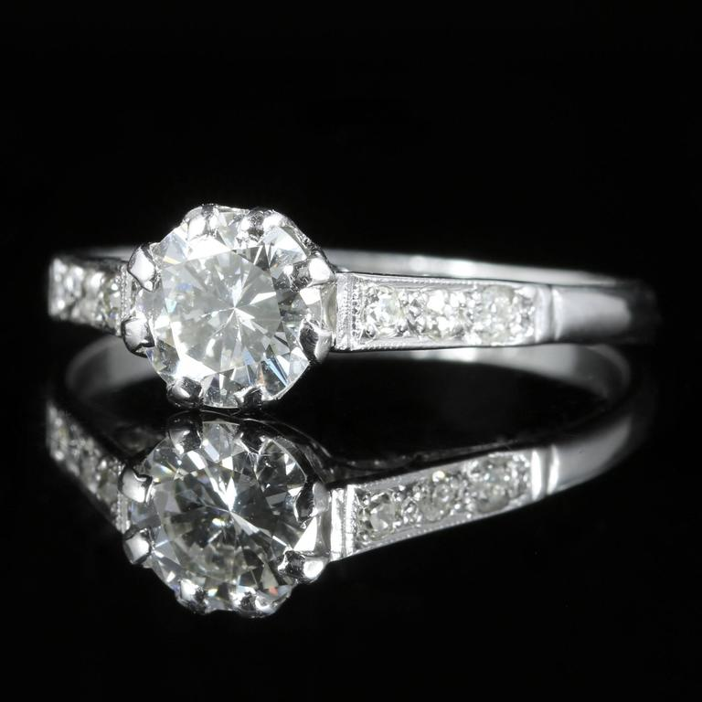 This spectacular Edwardian antique Platinum ring boasts a 0.90ct old cut Diamond which is original to the gallery.  Three Diamonds also chase down each shoulder, they are all superb colour cut and clarity - SI 1/2 H Colour.  Diamonds sparkle
