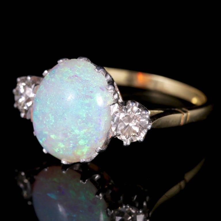 This fabulous natural Opal and Diamond trilogy ring is set in 15ct Gold, Circa 1900.  The central Opal measures 5ct.  The natural Opal is a kaleidoscope of rainbow colours shimmering and changing colours with thelight. They radiate a myriad of