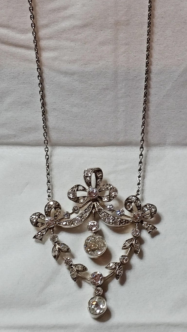 Golden Art Nouveau necklace of most elegant appearance,  looking like stylized flower's blossoms attached to leafy stems - these ones hung up at bows / meshes visible at top area.  Covered with various diamonds (vintage cuts), having 3.0 carat in