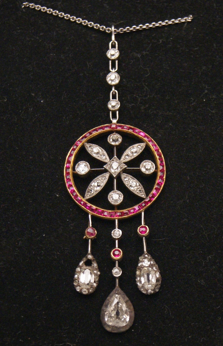 Golden Art Nouveau necklace of superb appearance - it is made in following manner: There is a ring hanging at pendant with diamonds existing / the ring covered with gemstones - rubies - surrounds a stylized floral arrangement with leaves.