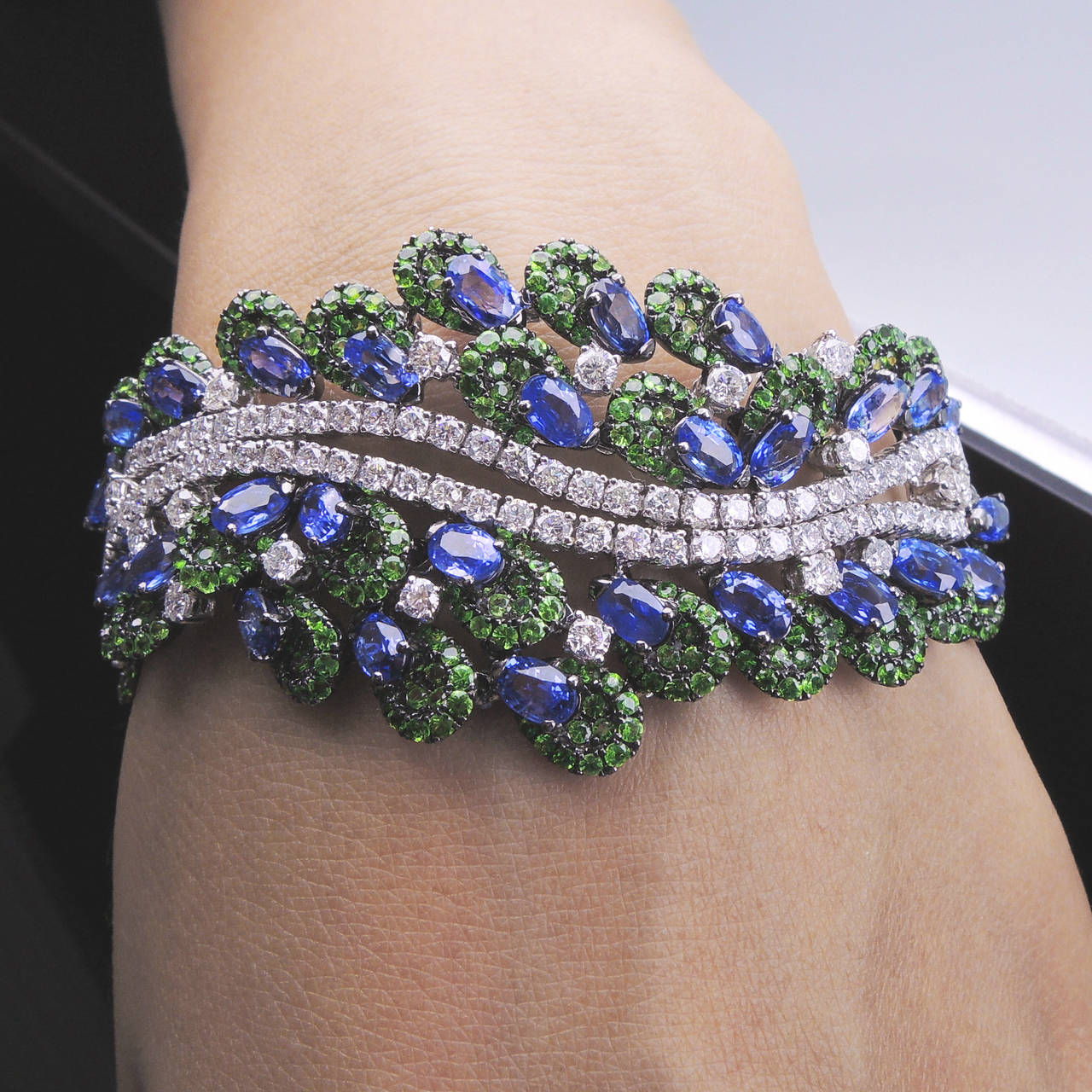 """Magnificent Diamond Sapphire Tsavorite Bracelet centered by two diamond Line bracelets surrounded by 42 oval sapphires=12.49ct, 532 tsavorite=6.09ct, 147 diamonds=5.12 ct; claw set in 18k white gold; approx. length: 7""""; approx. weight: 39.10gm."""