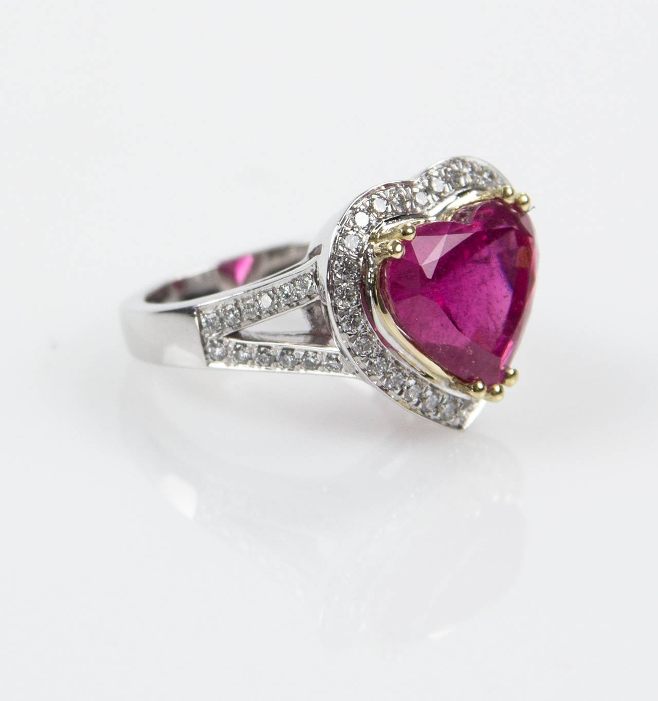 This Runway Rind centers a Beautiful 6.97ct Heart shaped Rubellite surrounded by fifty round brilliant cut diamonds, approx .75tctw; handmade 18k two-tone gold mounting; Ring size: 6.75. Classic and Timeless...For that Special Someone...including