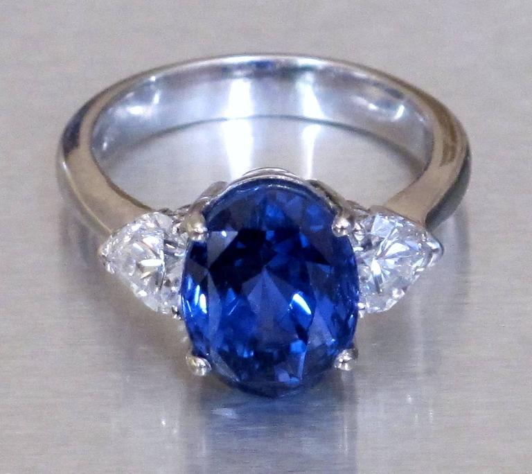 Beautiful and Timeless Ring, centered by one oval blue Sapphire, weighing approx. 6.42 ct; 11.00mm x 8.41mm x 7.61 mm, Sri Lanka no-heat, flanked by pair of heart shape Diamonds, total 0.92 ct, F-VS2, in hand made 18K white gold, prong settings.