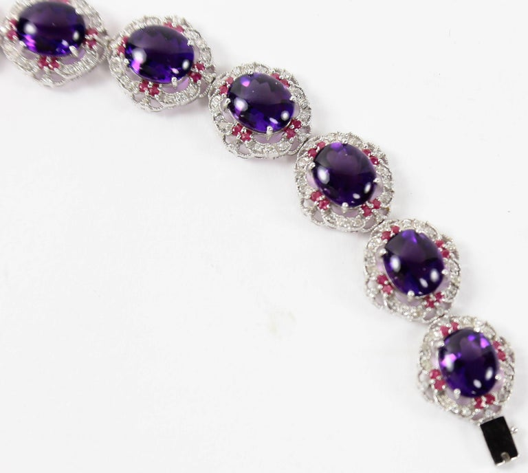 Stunning Contemporary flexible Runway design, featuring 14.22 carat of luscious cabochon and facet cut Amethyst. Each link set with 1.58 carat, enhanced by 16 brilliant diamonds and 8 facet cut Rubies. Beautifully Handcrafted in 18k white gold;