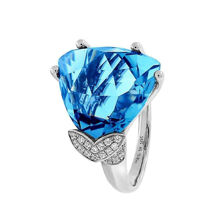 Beautiful Swiss-Blue Topaz ring accented by sixty-four brilliant-cut round Diamonds, extending to shank, weighing approx. 0.32 ct., triangular facet-cut Swiss-Blue Topaz measures approx. 16mmx16mm, approx. weight 16.4 ct.; mounted in 14k white gold