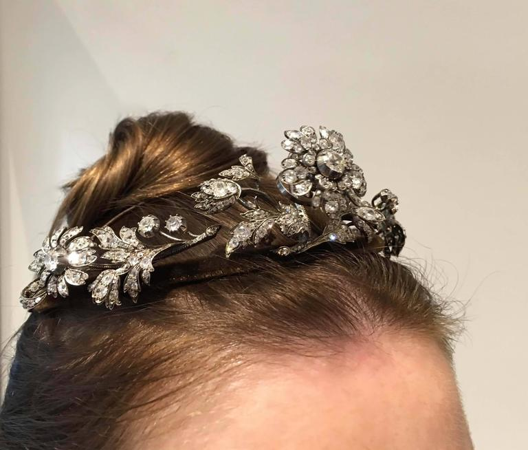 Diamond Tiara designed as a floral spray, the central flower en tremblant, with circular-cut, cushion-, pear-shaped, oval and rose diamonds, detachable tiara frame, three brooch clip fittings. Mounted in silver and backed in gold. Frame covered with