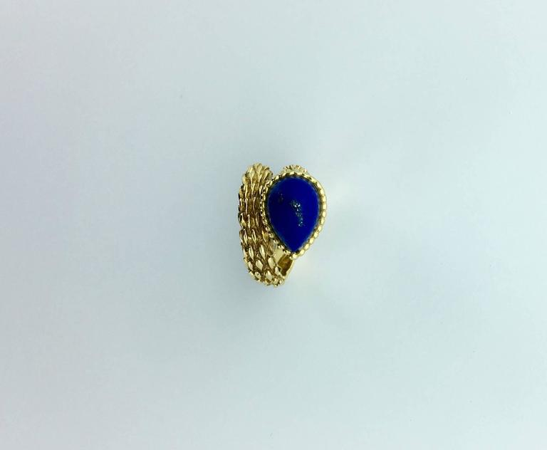 Designed as a textured bypass style band set with a pear-shaped cabochon lapis lazuli. Signed Boucheron French mark and maker's mark. Ring Size Us: 3 3/4 (46). Gross weight: 9.40 grams.