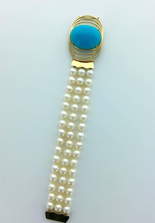 Perfect jewel for this Summer! The Turquoise is Oversized and absolutely perfect. The Blue is deeper than the Greek sky. Centering a yellow gold 18k 750 pattern with three strands of cultured pearls.  The center can be worm as a pendant on a