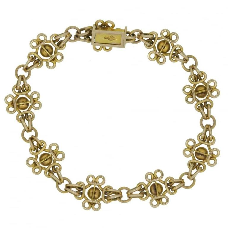 Late Victorian/early Edwardian era bracelet marked 15ct comprising nine decorative panels with a domed plain polished centre and looped wire surround.  These panels are connected to a round gold link by pairs of oval links to each side.  The