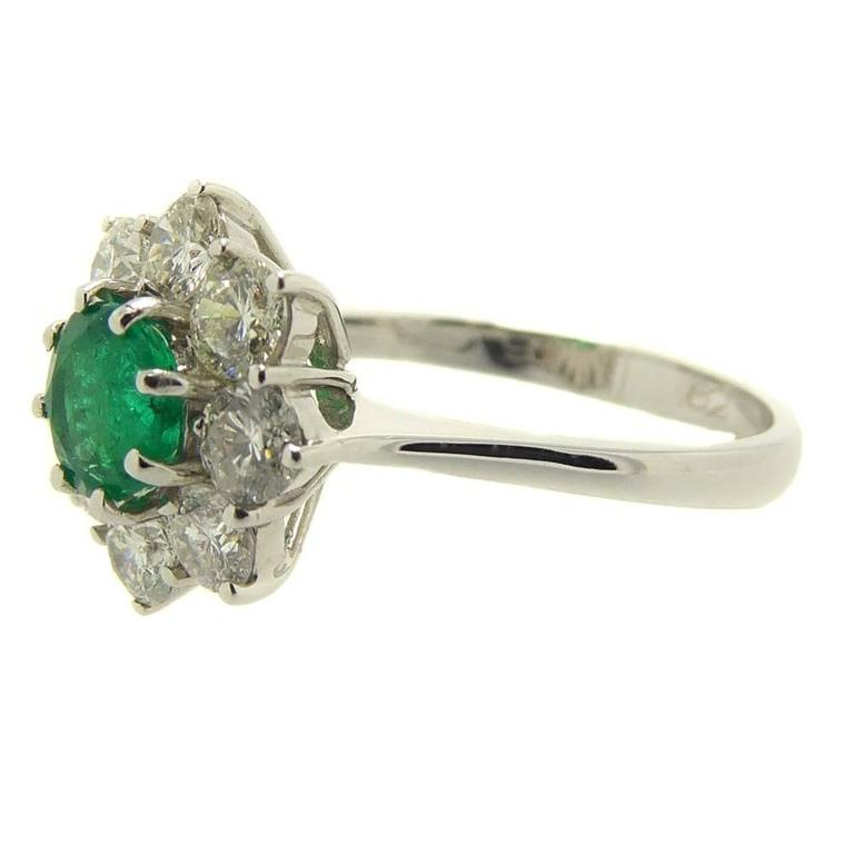 Classic style emerald and diamond cluster ring set to the centre with a round emerald of good strong green colour to a surround of eight very nice diamonds all claw set in white metal on a basket style mount.  Knife edge shoulders to a slight