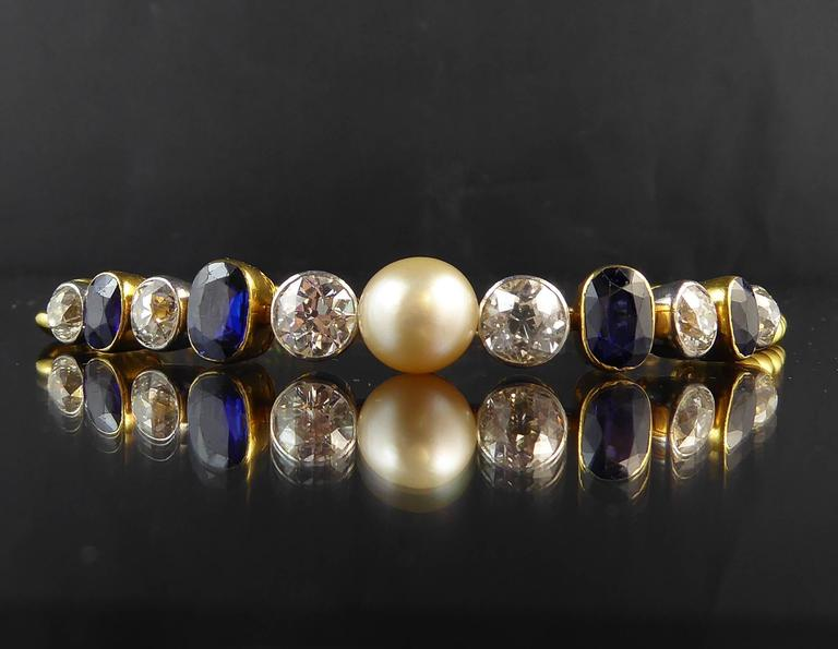 Created in the 1920s/1930s this imposing line bracelet centres on a large creamy white pearl, assessed as natural, and flanked on either side by three old European cut diamonds in white rub-over settings to articulated collets.  Between the diamonds