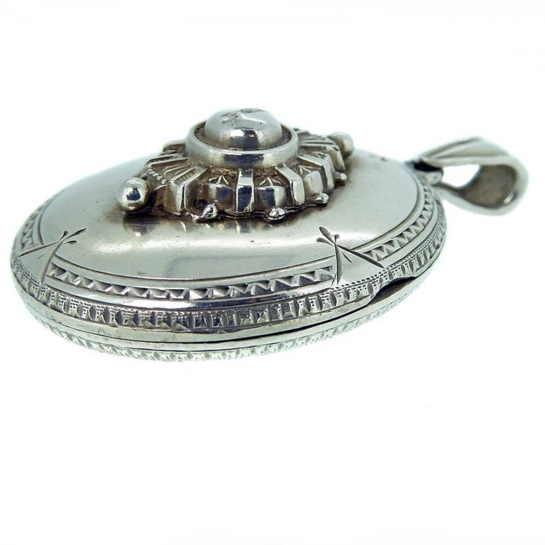 A very ornate silver locket with a delicately engraved edge to the front half and a typically Victorian raised motif to the centre of a central dome surrounded by a sunray and bead edge.  The reverse of the locket also boats some very pretty