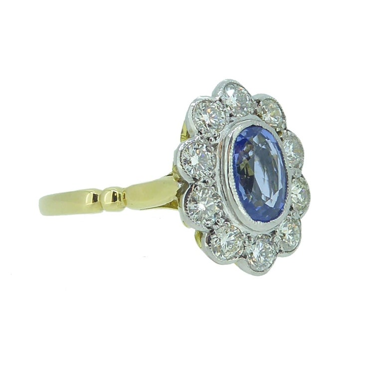 Popularised in the 1980s when Princess Diana became engaged with a sapphire and diamond cluster ring, the style continues its popularity even today.  This is a beautiful example set with an oval mixed cut, light violet-blue sapphire to the centre of