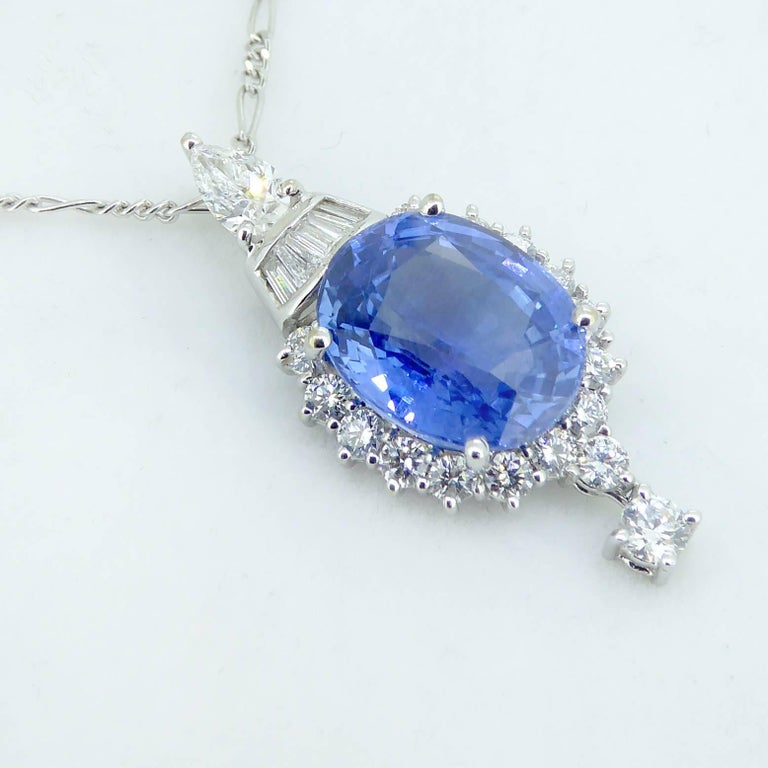 A beautiful pendant combining baguette, pear and brilliant cut diamonds with sapphire in a stunning evening wear or cocktail  necklace.  The pendant is set with an oval mixed cut sapphire of pale to medium blue surrounded by 16 brilliant cut