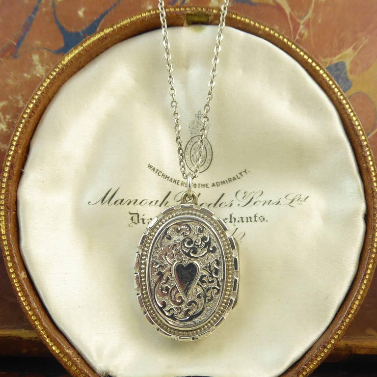 A really cute antique silver locket of very wearable proportions.  Dating from the later part of the Edwardian era, the locket  is very ornately hand engraved to the front with a raised oval border patterned with ancanthus leaf engraving in the