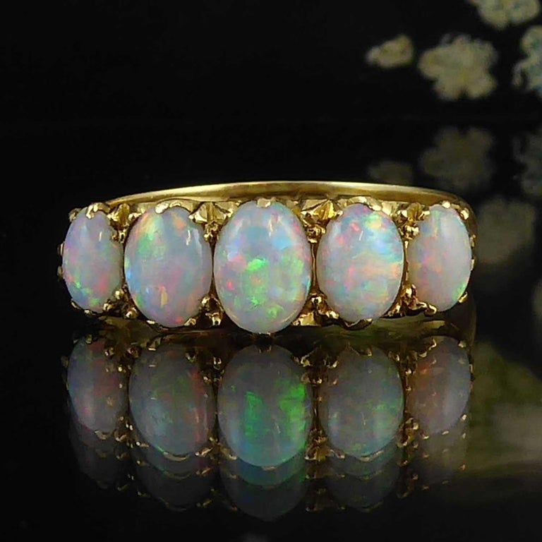 An antique opal ring set with five cabochon cut oval opals graduating in size from the centre opal at approx. 3.0mm x 5.0mm to 2.0mm x 4.0mm at each end. Displaying a play of blue, green and orange fire, the opals are complimented by the yellow gold