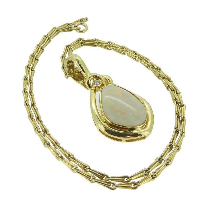 Something out of the ordinary with its off-oval shape and mirroring gold surround, this opal and diamond is set with a cabochon opal in a gold rub over setting compliments the rainbow hues of the of opal.  The single diamond feature at the top of