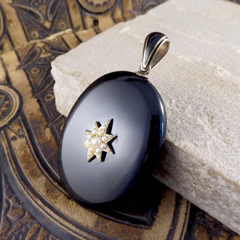 This charming antique pendant was crafted in the Victorian period. Set in black onyx with a pearl star motif there is a small compartment at the back for a memento of a loved one.  Highlighted with 15ct yellow gold and black enamel, it is a classic