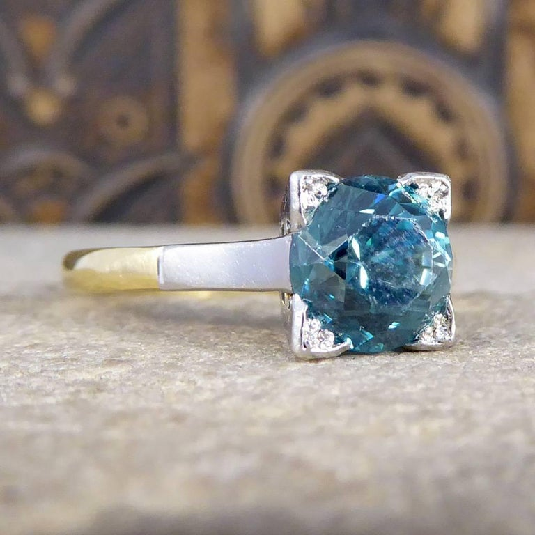 This gorgeous Art Deco ring features one single beautiful and vibrant blue Zircon, in a platinum square setting. The platinum setting has a simple and elegant design from the side profile and leads down the shoulders to the 18ct Yellow Gold band.