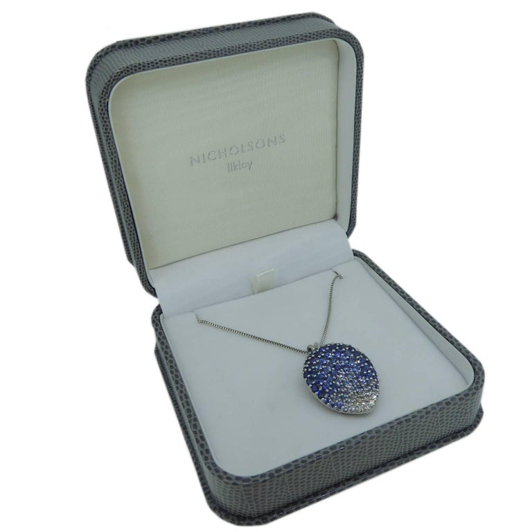 A very unusual pear shaped pendant pave set with brilliant cut diamonds are sapphires coloured blue and fading to white.  The pendant has a split chain runner in polished white metal and is complete with a platinyum box chain that fastens with a