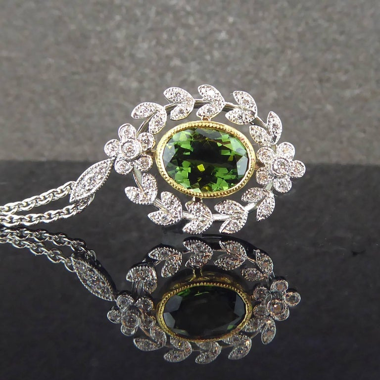 A refined an elegant antique style pendant created in the Belle Epoque style which lasted from the 1870s through to the outbreak of the 1st World War.  Set to the centre with an oval, mixed cut green tourmaline of deep and rich hue in a contrasting