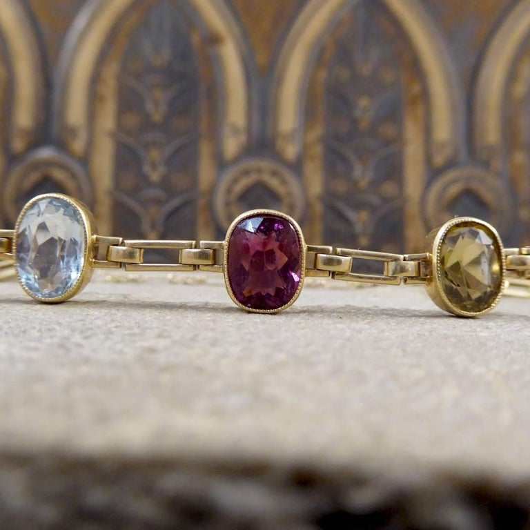 This gorgeous Edwardian bracelet has been hand crafted in 15ct Yellow Gold, and is adorned with five colourful gemstones. Consisting of Tourmaline, Aquamarine, Garnet and Citrene stones in a rub over collar setting with a milgrain edge, a lovely