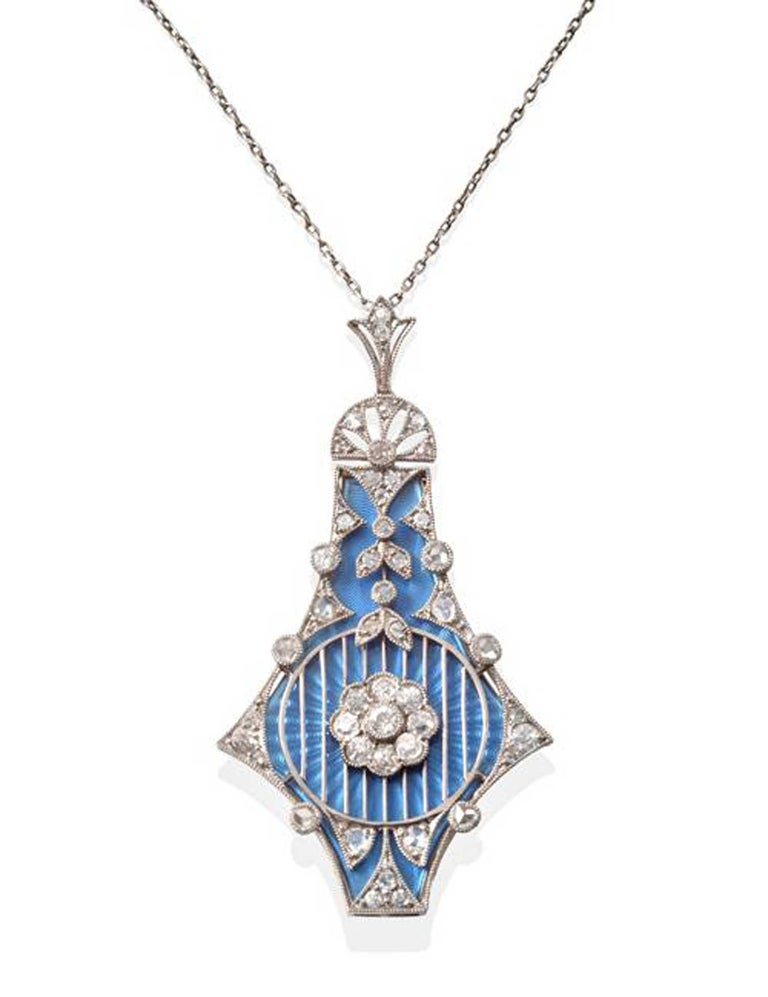 An antique diamond and enamel pendant in the Belle Epoque style with three interchangeable guilloche enamel plaques, one each in pink, pale blue, and mid-blue.  The pendant outline is in the form of an abstract kite-shape pendant measuring 1.96