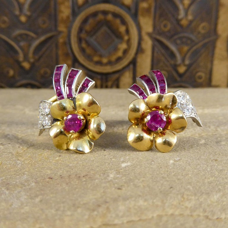 This lovely 1950's Earring and Pin set have been crafted from 18ct Yellow Gold and adorned with both Rubies and Diamonds. These clip on Earrings are very well matched showing flowers beautifully decorated with gems. The set is completed with a