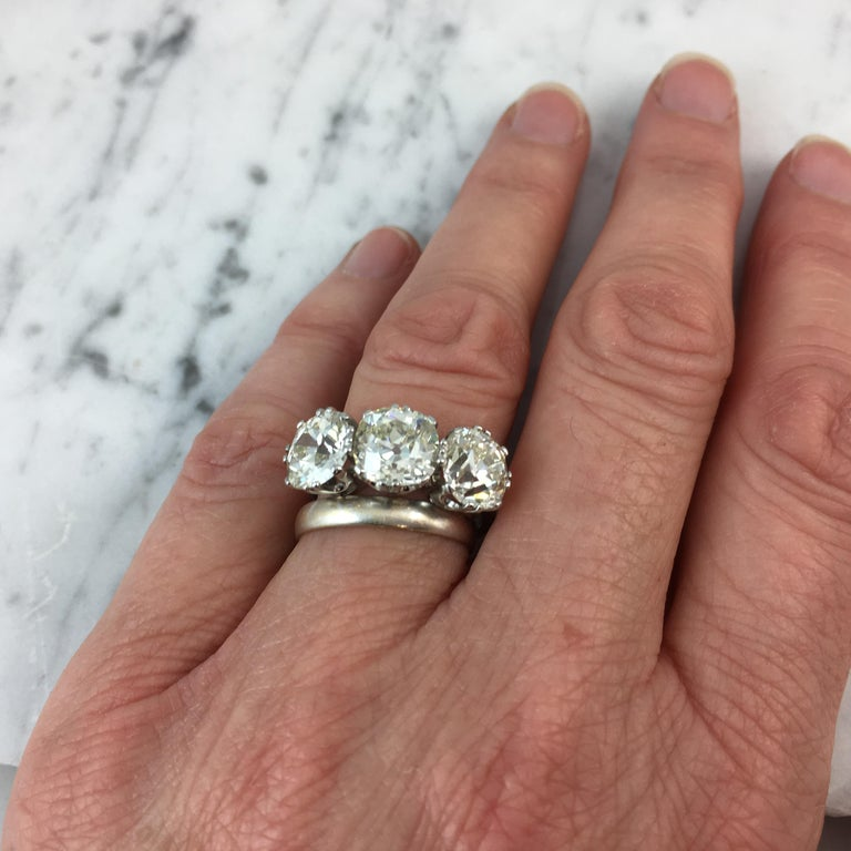 A spectacular three stone diamond ring set with three cushion shaped old European cut diamonds with weighed carat weights of 2.27ct, 2.72ct and 2.40ct.  The colour ranges from approximately N to tinted with clarity from VS1 to SI giving a lovely