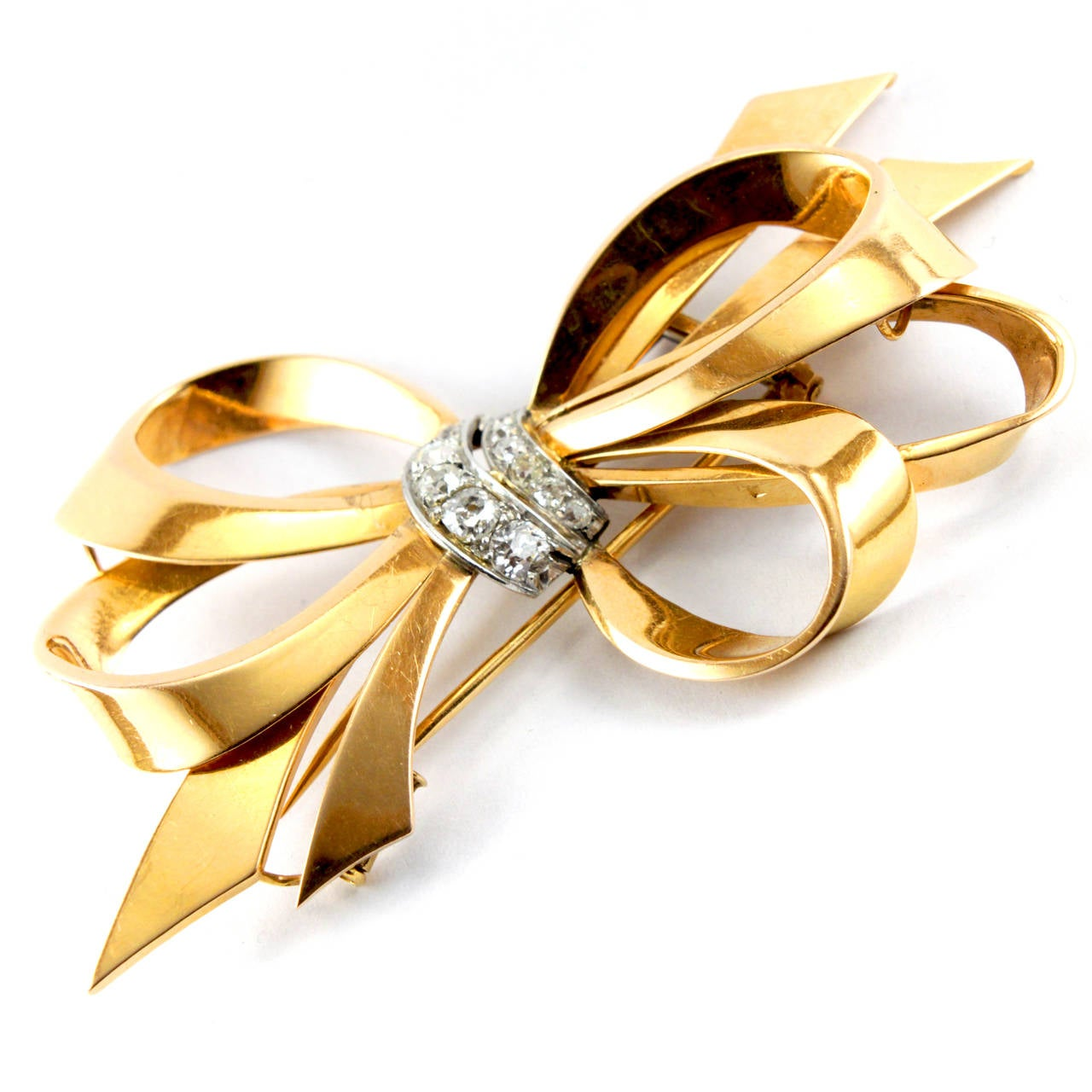 Cartier Gold and Diamond Brooch  A very glamorous and chic Ribbon Bow Brooch by Cartier Paris from the 1940s. It is set with circa 2 carats of old cut diamonds in 18k yellow gold. Signed.