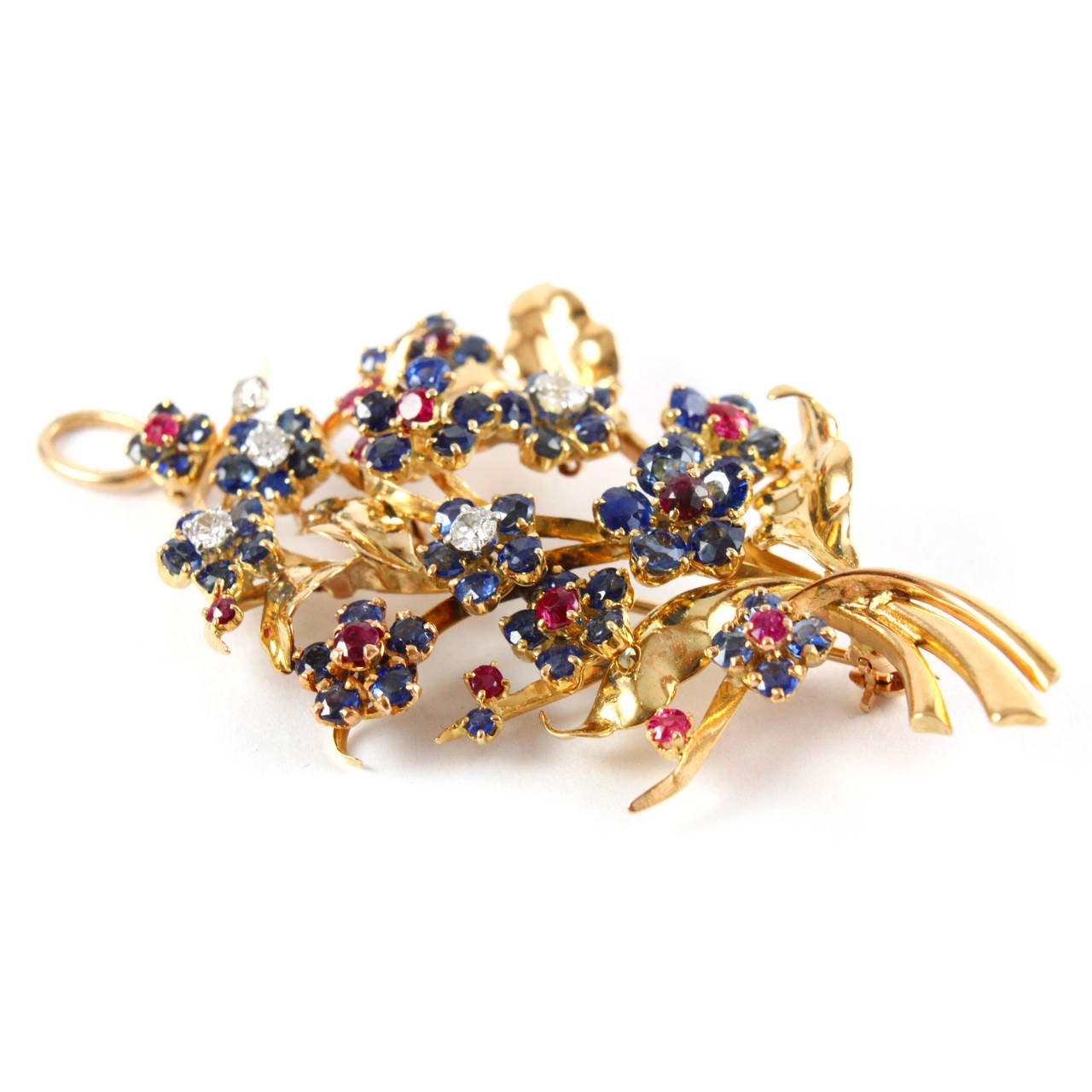 A charming flower brooch/pendant by Mauboussin.  Composed with rubies, sapphires and diamond solitaires and made in 18k yellow gold. The jewel has a pendant hook as well as a brooch pin.  Signed Mauboussin Paris, numbered, with French