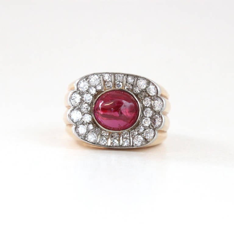 A very impressive retro ring in 18k gold with a big natural unheated Burma ruby cabochon, 5.5ct (the weight of ruby is inscribed in the ring). The ruby centre stone is surrounded by brilliant cut diamonds, ca. 1ct. The beautiful ring strongly