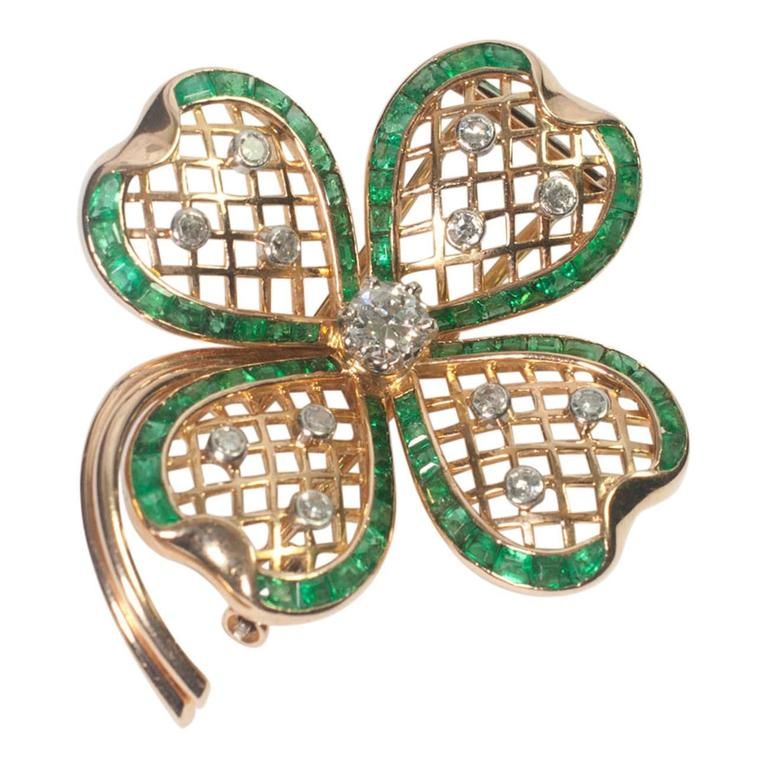 Beautiful Mauboussin emerald and diamond shamrock brooch formed of four leaves in a trelliswork design.  Each leaf is edged with calibre cut emeralds of a vivid green colour and set with three single cut diamonds weighing a total of 0.36ct.  In the