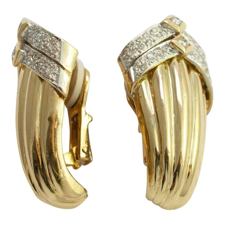 Dramatic, large, 18ct gold and diamond clip-on earrings.  These are in a ribbed gold design with diamond set chevrons at the top.  The brilliant cut diamonds weigh 1ct.  The earrings are for non-pierced ears and are fixed with a strong gold clip.