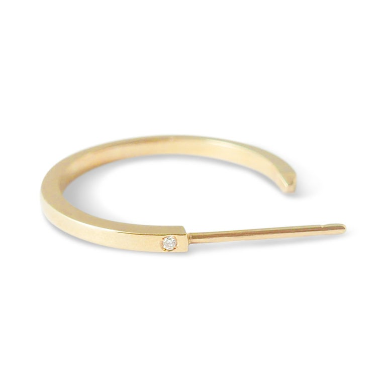 Clean-lined and minimalist, these solid 18-karat gold hoop earrings feature two tiny H-VS1 diamond accents on each hoop.  Measuring 1.9 cm in diameter, the hoops feature a classic post and butterfly fastening.   Handmade in London.  Hallmarked 750