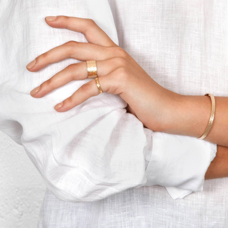 This simple band ring features a rustic shimmering texture handcrafted in 18-carat yellow gold.  In stock in UK size G (US size 3 3/8), UK size F 1/2 (US size 3 1/8), and UK size M (US size 6).  Can be resized at no charge upon request.  Every piece