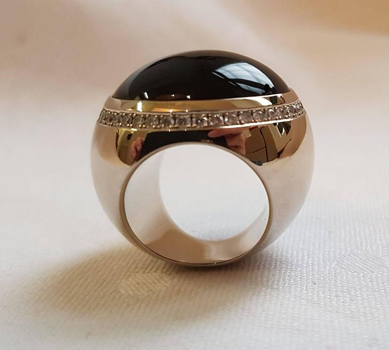 Extravagant design ring made by Wagner Preziosen. 18 carat white gold, onyx cabochon surrounded by 44 diamonds 0.88 carats. Ring size: 53 (European Size). A flashy ring for outgoing personalities.