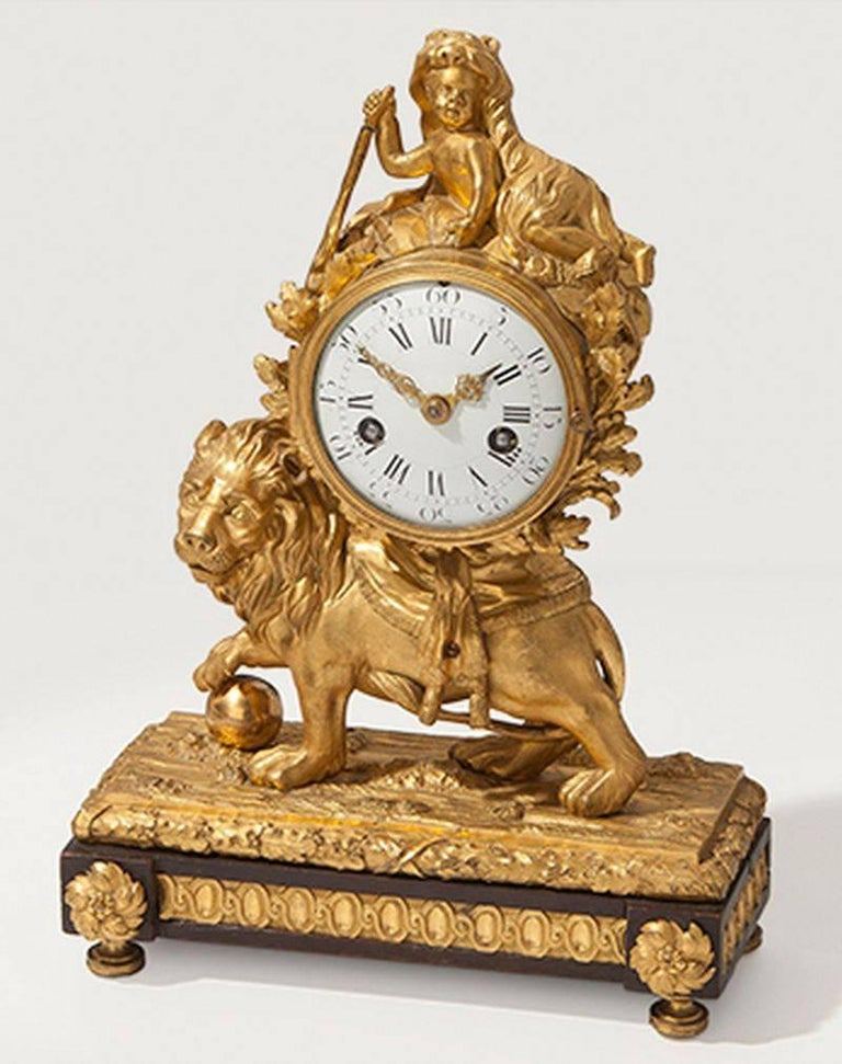 Eyecatching gilded bronze lion mantle clock, Louis XV, circa 1770. 3.5 inch enamel dial; bell striking movement with flat-bottomed plates and outside countwheel. The drum case surmounted by a putto draped with a lion's pelt and raised on the back of