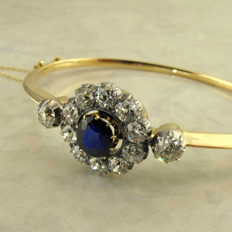 14k yellow gold and silver antique Victorian sapphire and diamond bangle bracelet. The knife edge bangle fitted with a one piece removable top featuring a center round AGL certified natural untreated sapphire measuring 7.29 x 6.40 x 3.86 mm, with an