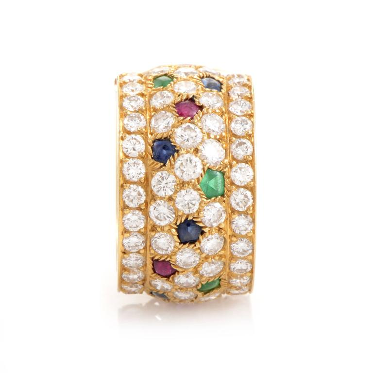 The brilliance of Cartier design makes a kaleidoscopic showcase in this stunning ring. The wide expanse of its 18K yellow Gold band provides plenty of room for sapphires, emeralds and rubies to add vibrant color to a generous tide of 5.00ct