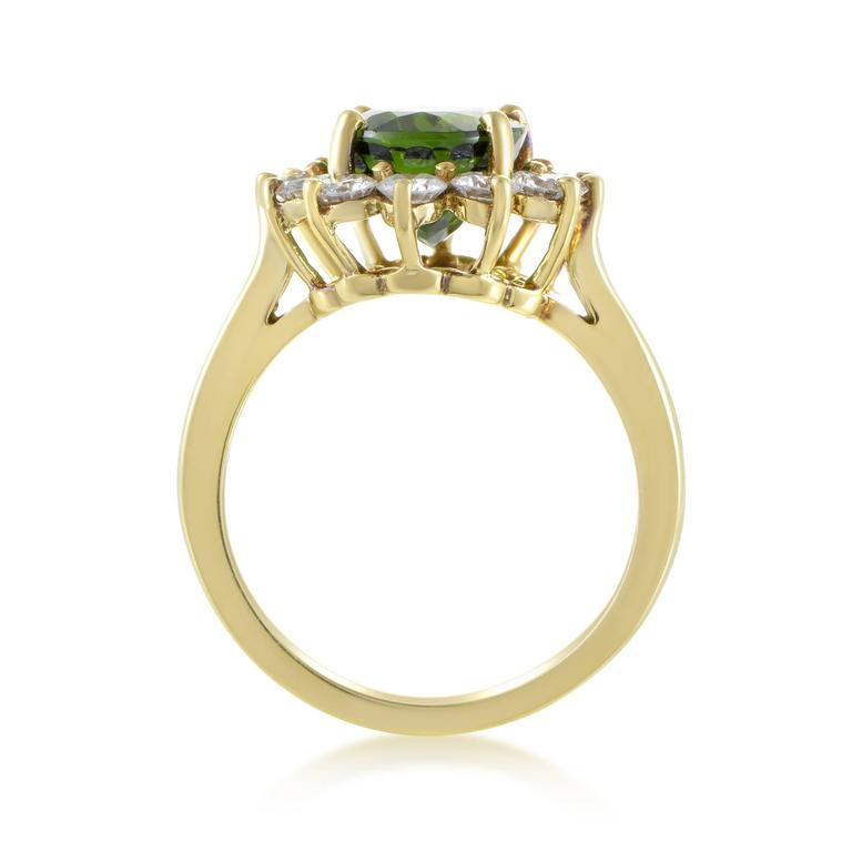 Providing a wonderful backdrop for the majestic beauty and exquisite cut of the remarkable green tourmaline weighing 3.00 carats, the neat arrangement of glittering diamonds amounting to 0.75ct adds a stunning final touch to this 18K yellow gold