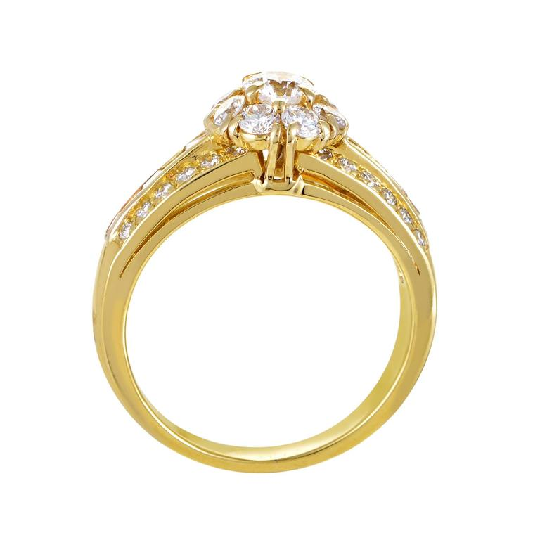 This lovely ring from Van Cleef & Arpels features a classic design that is perfect for any lady. The ring is made of 18K yellow gold and features shanks set with diamonds. as well as a floral-shaped motif comprised of diamonds topping off the