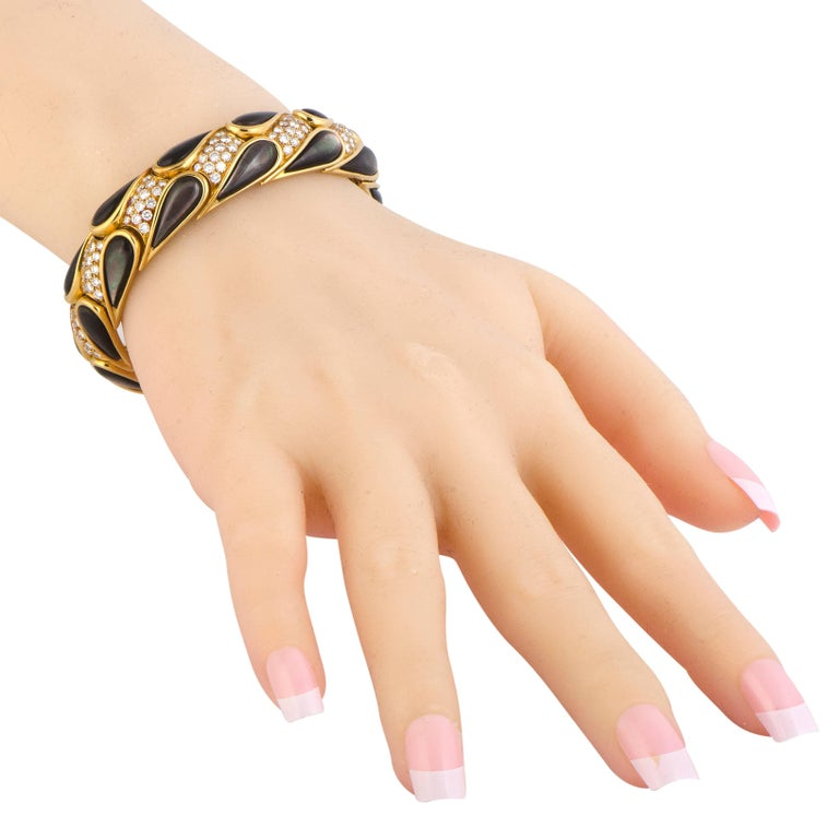 Bold and stunningly fashionable, this remarkable bracelet is designed by Mauboussin and boasts incredibly offbeat, eye-catching appearance. The bracelet is made of radiant 18K yellow gold and it is embellished with black mother of pearl and