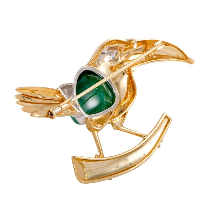 Depicting a bird in an exceptionally luxurious manner, this eye-catching brooch offers an incredibly offbeat, fashionable appearance. The brooch is made of 18K yellow gold and platinum decorated with 0.12 carats of diamonds and a captivating emerald