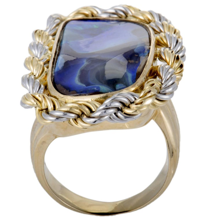 Featuring an incredibly unconventional combination of 18K yellow and white gold and opal, this fascinating ring offers a stunningly fashionable appearance. The opal weighs 18.99 carats. Ring Top Dimensions: 38mm x 23mm Band 7mm Top 7mm Ring Size 6.75