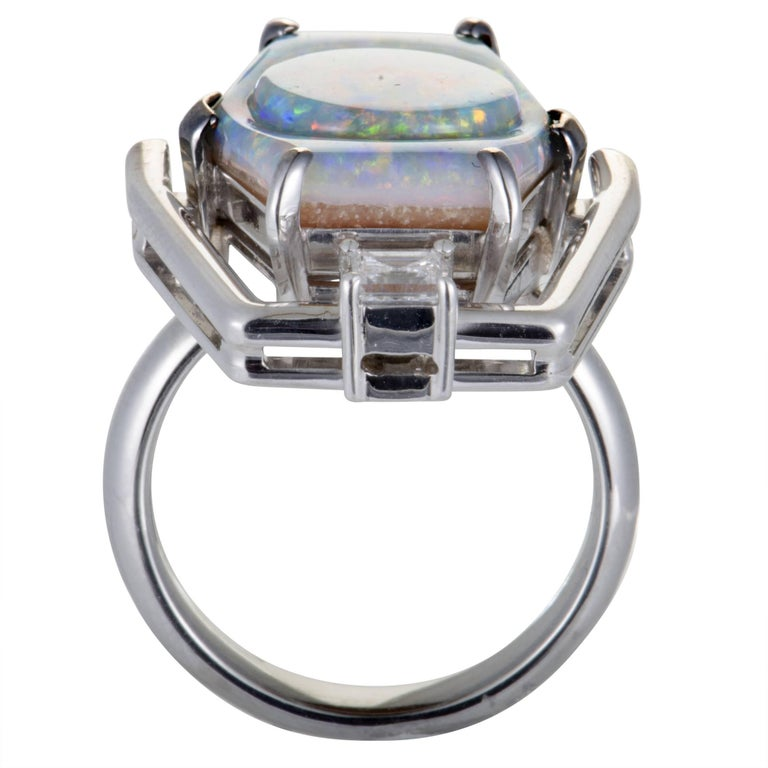 Unconventionally designed and set with an eye-catching opal cut in an incredibly offbeat manner, this extraordinary ring offers an exceptionally fashionable appearance. The ring is made of platinum and boasts an opal and a diamond stone that weigh