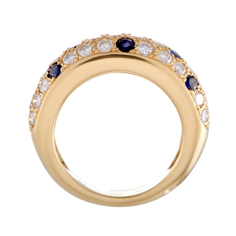 The enchanting radiance of 18K yellow gold brings out in a most luxurious fashion the sublime resplendence of diamonds and the regal allure of sapphires in this exceptional ring that is designed by Cartier. The diamonds boast grade E color and VS