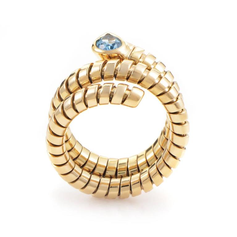 With serpentine sleekness this Tubogas ring wraps snugly three times in a glamorous grasp of 18K yellow gold. Leading this rivulet of precious slivers is the ripe setting of topaz that punctuates the ring's rippling curves. Compelling style and
