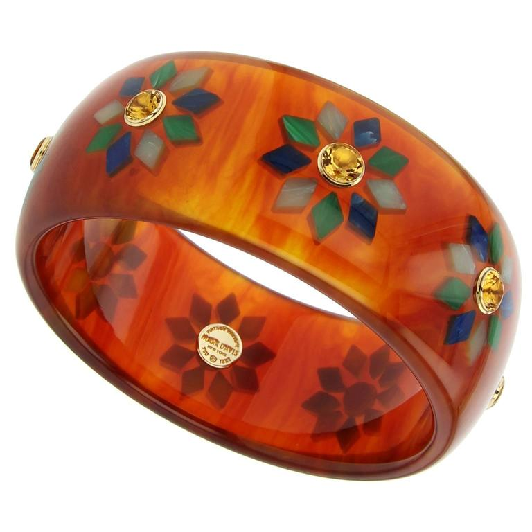 This unique and bold Mark Davis Collector bangle was handcrafted using vintage tortoise bakelite.  The geometric motif was precisely inlaid with diamond-shaped pieces of green and blue bakelite.  Each station is centered with a citrine, bezel-set in