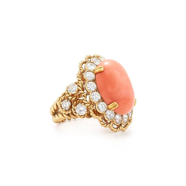 Set with a cabochon coral within a round brilliant diamond surround flanked to either side by three round brilliant diamonds to the 18k gold twisted rope shank and detail, mounted in 18k gold  Coral Cabochon measures approximately 19.0 by